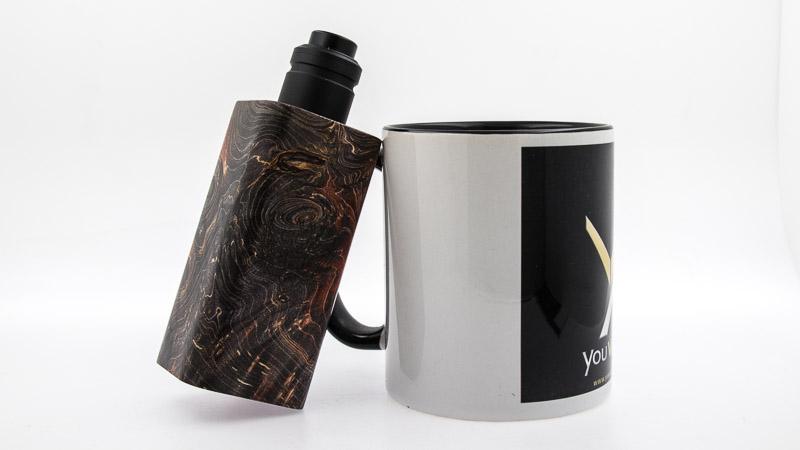 associée au dripper double coilAxial ProdeTwisted MessesetMass Mods a cote d'une tasse youvape