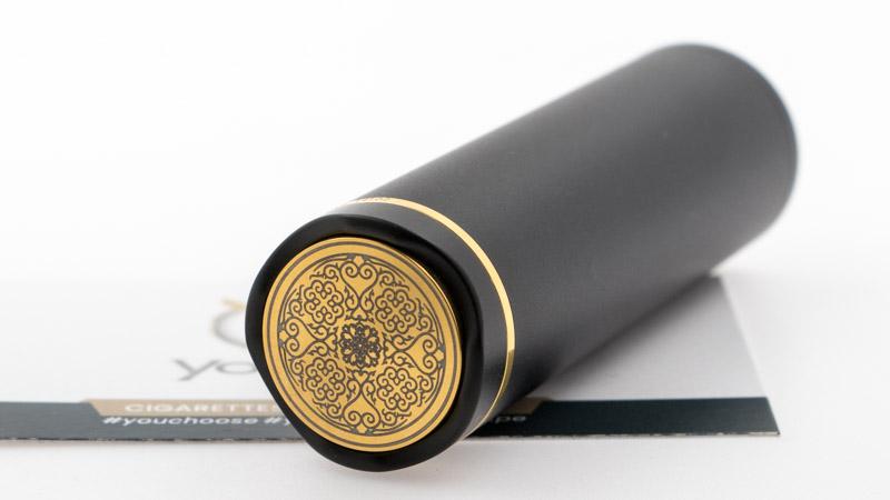 Le bottom cap du mod accueille un switch dorée, gravé des motifs traditionnels de Domod.